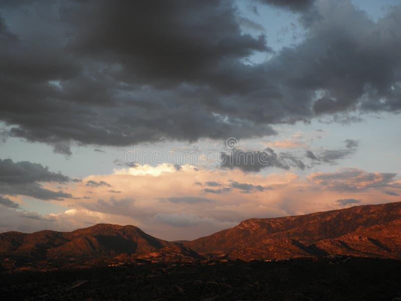 Monsun fördunklar solnedgång över de Pusch Ridge bergen i det Tucson Arizona landskapet arkivbild