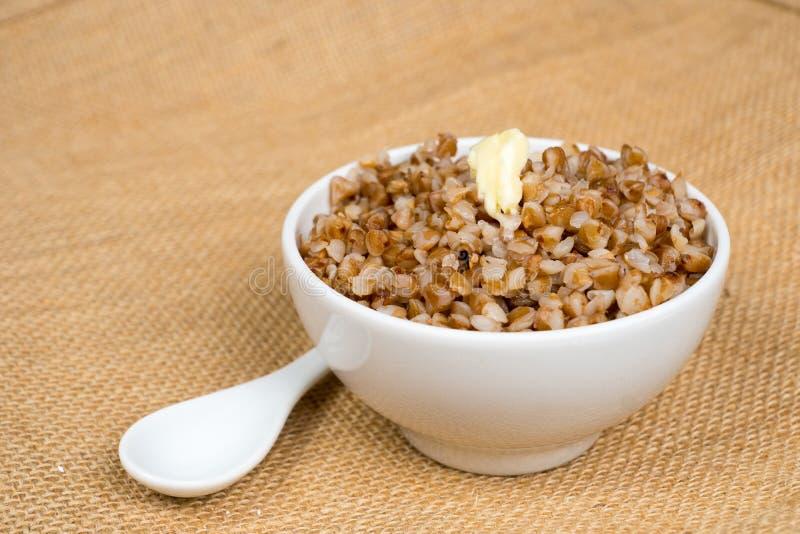 Montão cozinhado do trigo mourisco com manteiga na bacia branca imagens de stock royalty free
