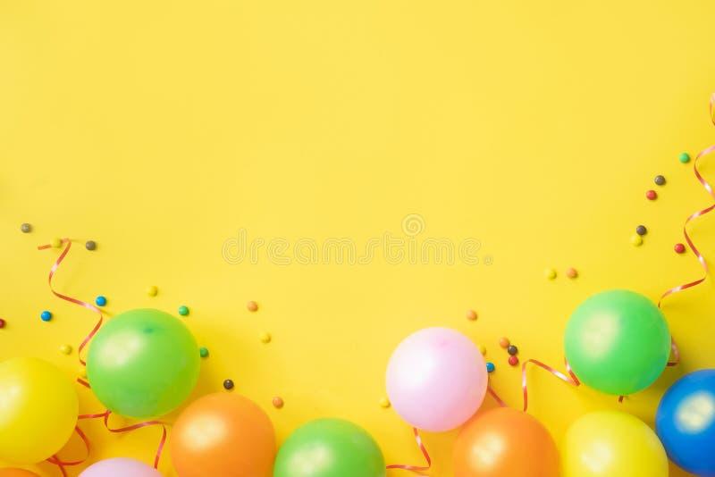 Montão de balões, de confetes e de doces coloridos na opinião de tampo da mesa amarela Fundo da festa de anos Cartão festivo fotografia de stock royalty free