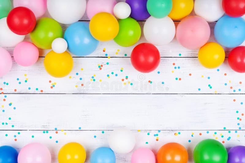 Mont?o de bal?es e de confetes coloridos na opini?o de tampo da mesa branca Fundo festivo ou do partido Configura??o lisa Cart?o  foto de stock royalty free