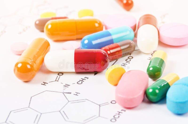 Montão de comprimidos e de tabuletas da cor em fórmulas químicas imagem de stock