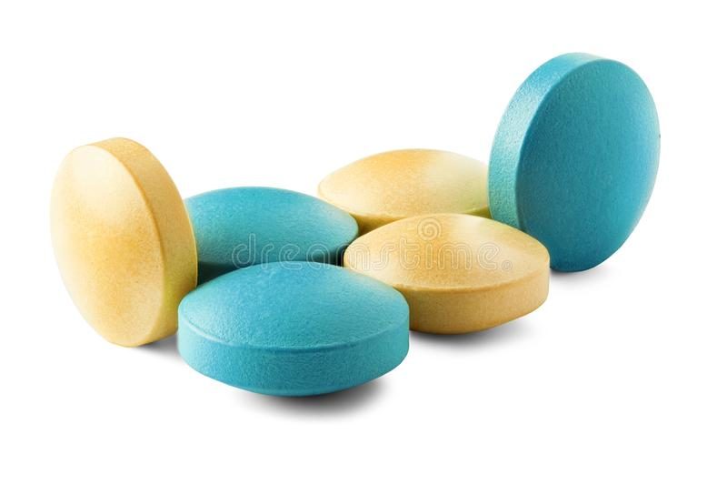 Montão de comprimidos médicos na cor amarela e verde, com sombras no fundo branco isolado Comprimidos com forma redonda imagem de stock