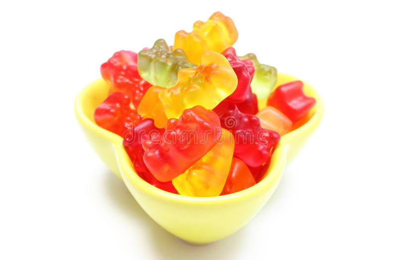 Montão de doces coloridos do urso do haribo na bacia amarela Fundo branco foto de stock royalty free
