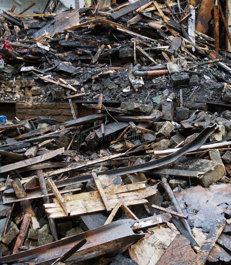 Montão de feixes e da entulho queimados e dispersados dos tijolos após um fogo em uma grande construção imagem de stock
