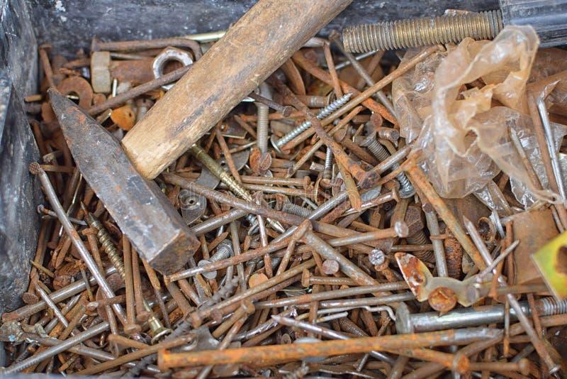 Montão de pregos e dos parafusos oxidados velhos na parte inferior da lata com martelo foto de stock