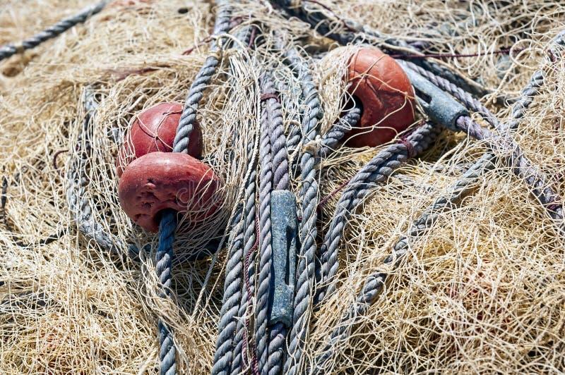 Montão de secar a rede de pesca amarela com flutuadores vermelhos imagem de stock