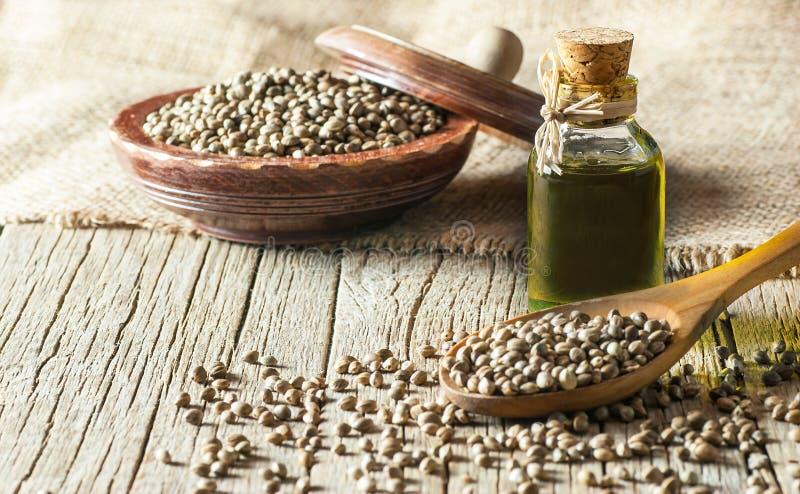 Montão de sementes de cânhamo orgânicas secadas ou de sementes da planta do cannabis na colher e na bacia com vidro do óleo de se imagem de stock royalty free
