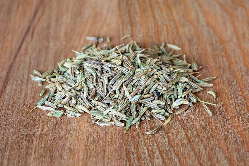 Mont?o de sementes da alcaravia ou de cominhos em uma placa de corte de madeira marrom Especiarias e temperos naturais do aliment foto de stock