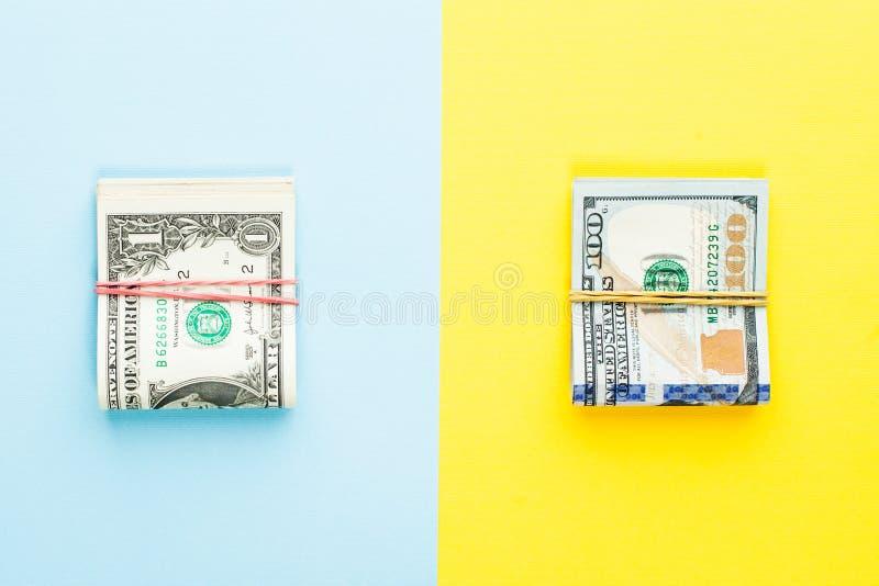 Montão de um dólar de cédula e de cem moderno nós notas de dólar no fundo azul e amarelo Lucro comercial do investimento do dinhe imagem de stock