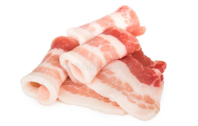 Montão do bacon cru rolado das partes isolado no branco imagens de stock