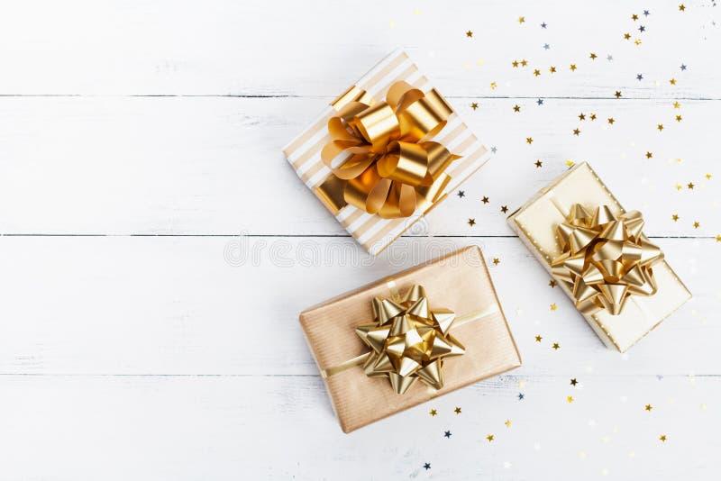 Montão do presente ou dos confetes atuais das caixas e das estrelas na opinião de tampo da mesa de madeira branca Composição lisa foto de stock royalty free