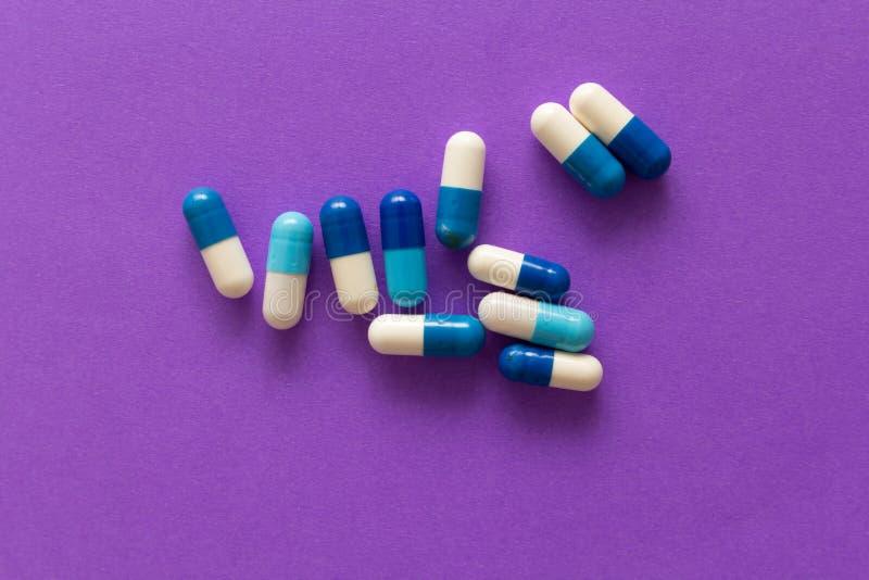 Montão dos comprimidos espalhados sobre a tabela de cor Grupo de branco sortido fotografia de stock