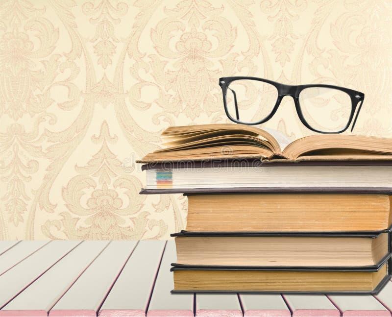 Montão dos livros com opinião do close-up dos vidros fotos de stock royalty free