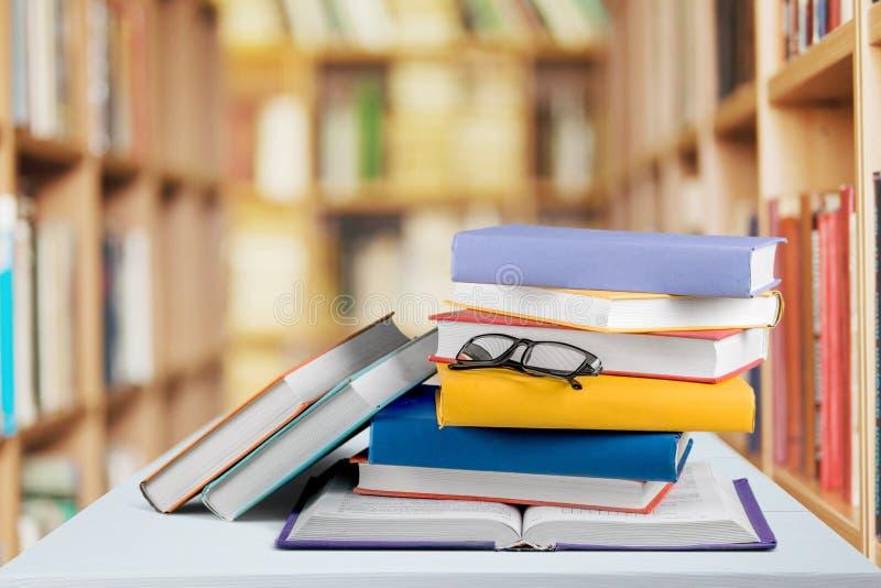 Montão dos livros com vidros na tabela de madeira imagem de stock