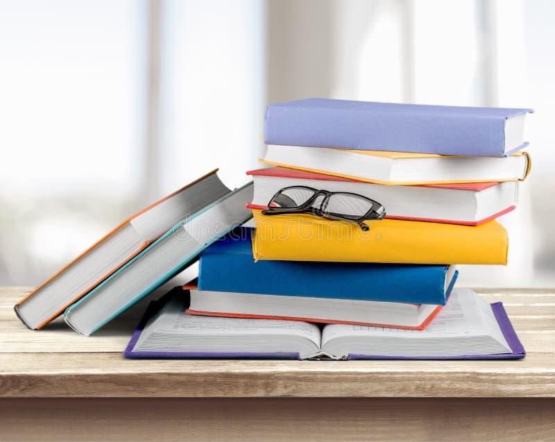 Montão dos livros com vidros na tabela de madeira imagens de stock