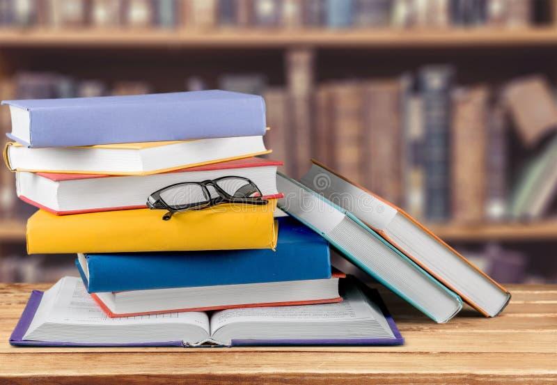 Montão dos livros com vidros na tabela de madeira imagem de stock royalty free