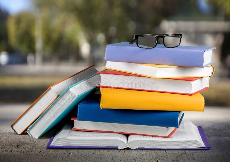 Montão dos livros com vidros na tabela de madeira fotografia de stock royalty free