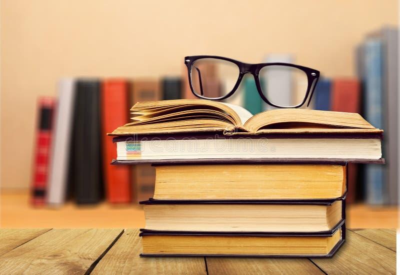 Montão dos livros com vidros na tabela de madeira fotos de stock royalty free