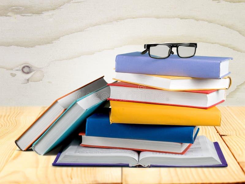 Montão dos livros com vidros na tabela de madeira foto de stock royalty free