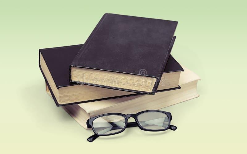 Montão dos livros com vidros no fundo claro fotos de stock