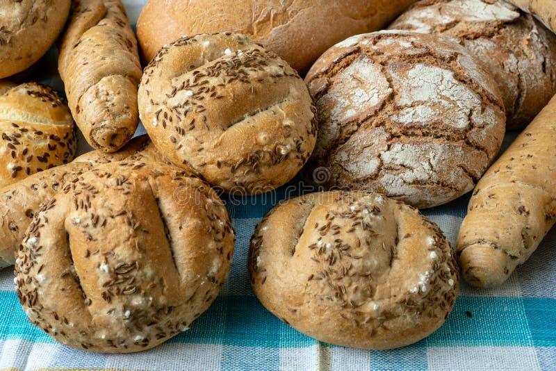 Montão dos vários rolos de pão polvilhados com o sal, alcaravia imagens de stock