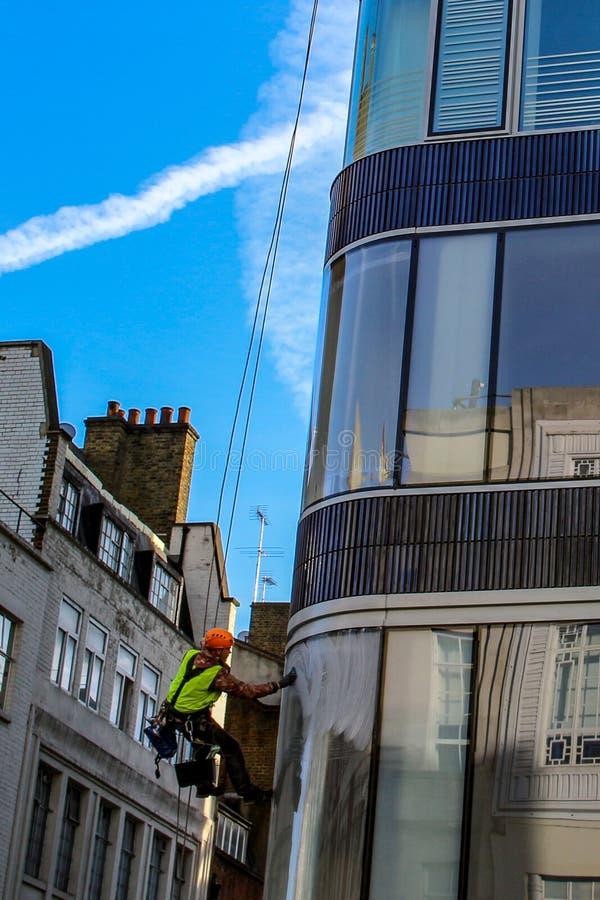 Montée d'homme dehors pour le verre de fenêtre de nettoyage de la haute tour photo stock