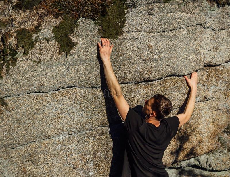 Montée de grimpeur de jeune homme sur la roche dans la petite pierre de fente photos stock