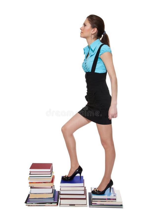 Montée de jeune femme sur des escaliers des livres photo libre de droits