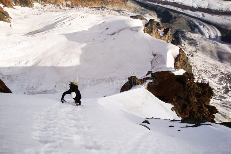 Montée soloe gratuite masculine de grimpeur de montagne de jeune Ridge sur le visage du nord de Breithorn dans les Alpes suisses photographie stock
