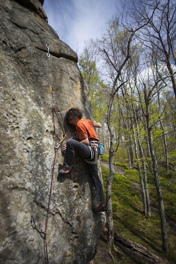 Montées d'athlète sur la roche avec la corde photos stock