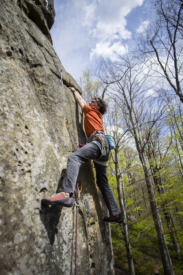 Montées d'athlète sur la roche avec la corde image libre de droits