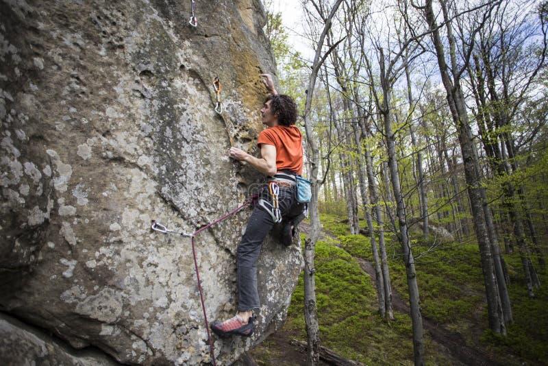 Montées d'athlète sur la roche avec la corde photo libre de droits