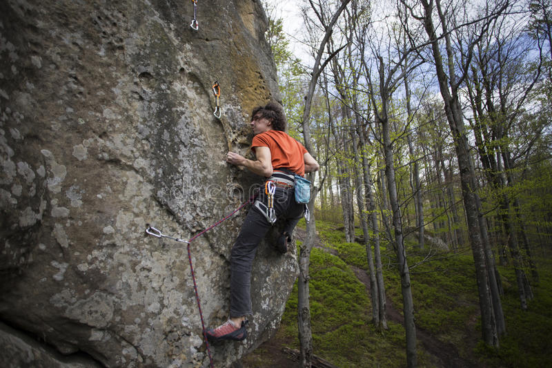 Montées d'athlète sur la roche avec la corde photographie stock