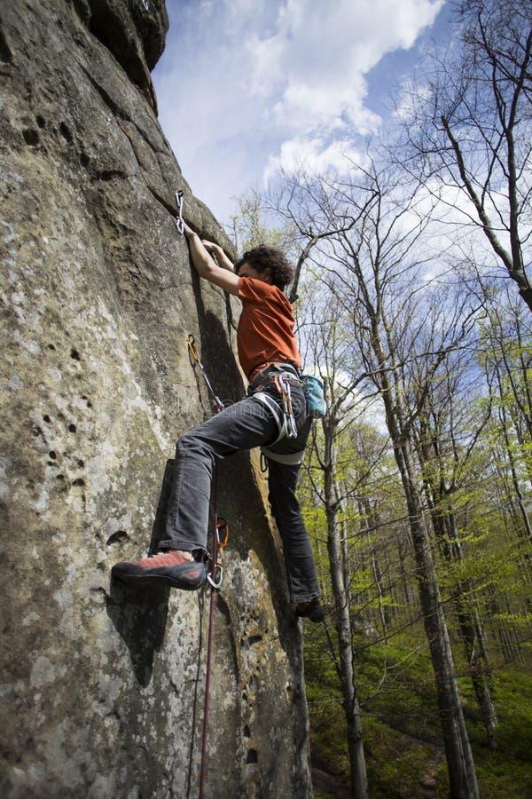 Montées d'athlète sur la roche avec la corde photographie stock libre de droits