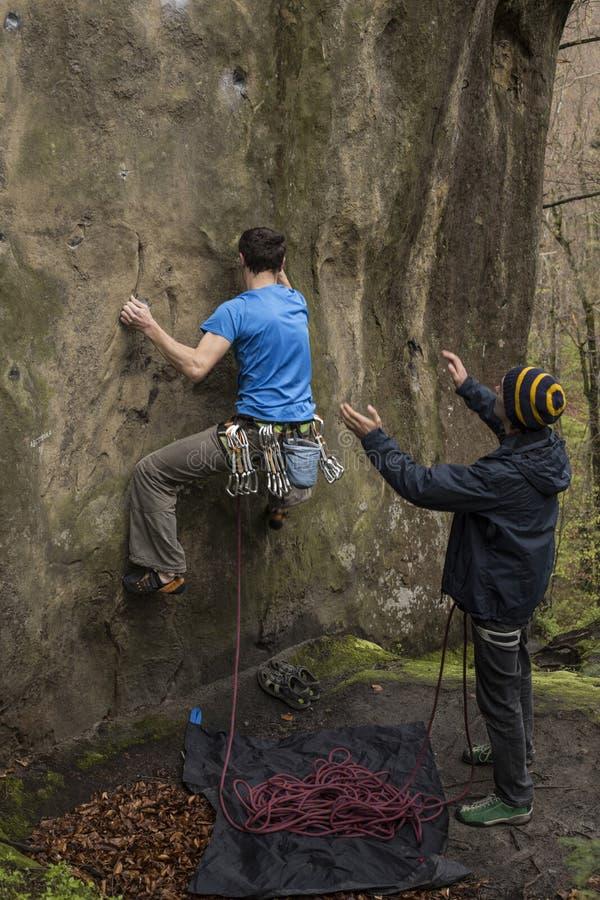 Montées d'athlète sur la roche avec la corde images libres de droits