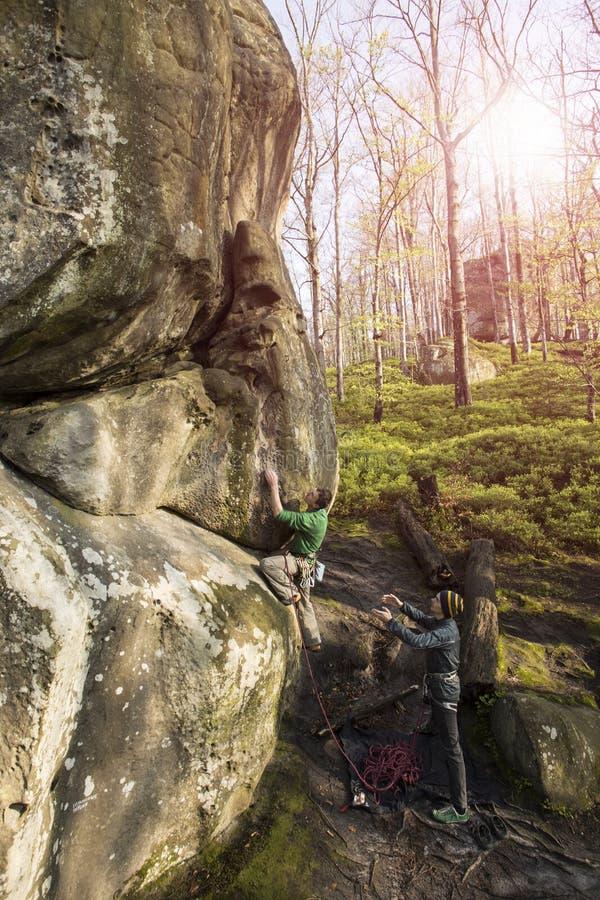 Montées d'athlète sur la roche avec la corde images stock