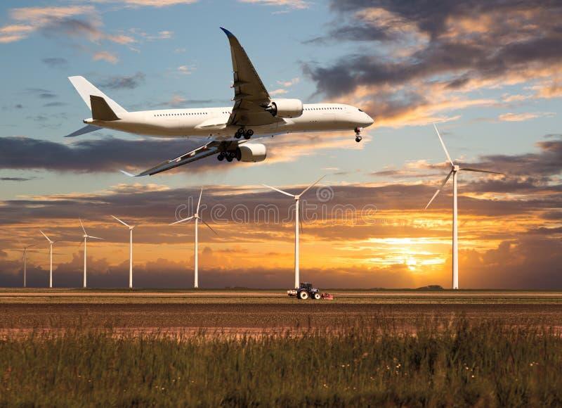 Montées d'avion de passagers au-dessus du champ de ferme images stock
