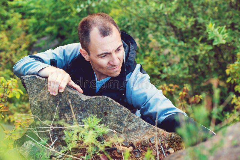 Montées d'homme sur la roche Grimpeur masculin réussi fort Homme montant la roche de montagne Concept de mode de vie, d'extrémité photographie stock libre de droits