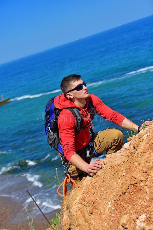 Montées d'homme sur une falaise image stock