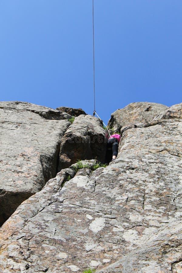Montées de grimpeur de roche de fille sur une roche image stock
