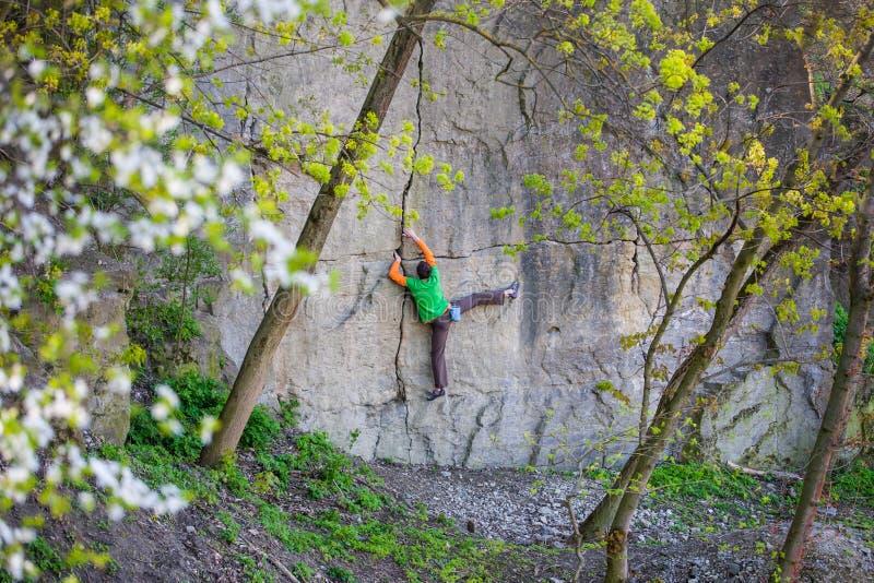 Montées de grimpeur sur la roche photo stock