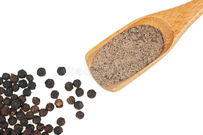 Montón ascendente cercano de la pimienta negra, granos de pimienta aislados en el fondo blanco imagen de archivo
