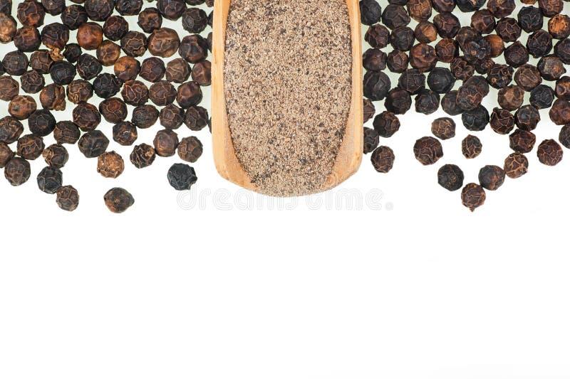 Montón ascendente cercano de la pimienta negra, granos de pimienta aislados en el fondo blanco fotos de archivo