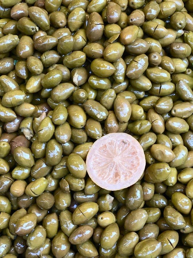 Montón de aceitunas verdes en el mercado del bazar del mercado con textura del limón/del fondo de la pila imagenes de archivo