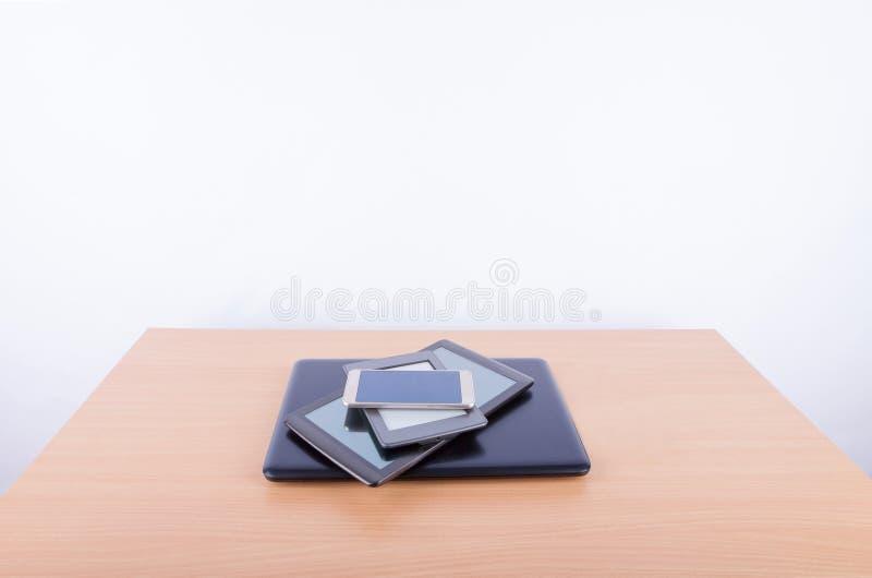 Montón de artilugios electrónicos en un escritorio de oficina foto de archivo
