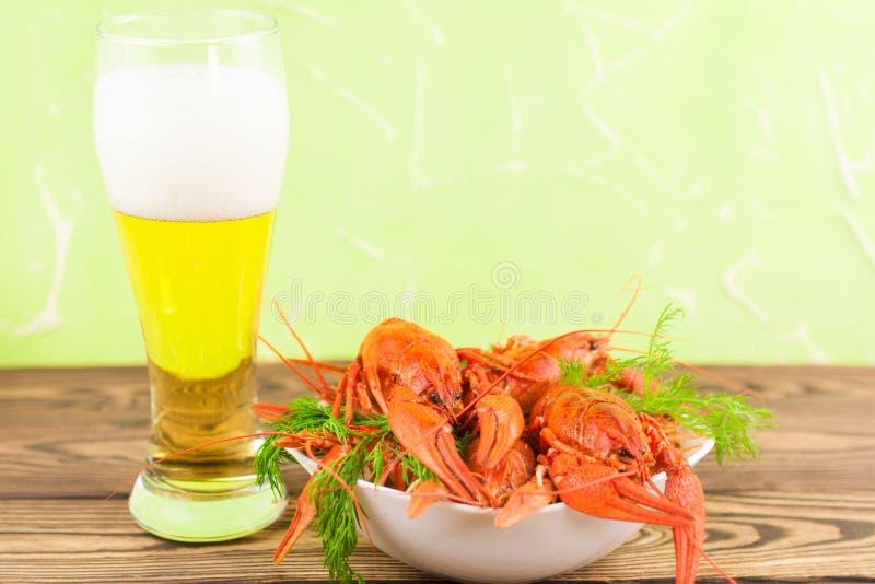Montón de cangrejos hervidos rojos con eneldo fresco en el cuenco de cerámica blanco cerca del vaso de cerveza lleno con espuma fotografía de archivo libre de regalías