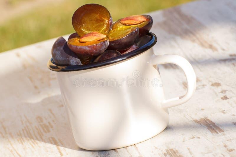 Montón de ciruelos en taza metálica en la tabla de madera en jardín el día soleado imagen de archivo libre de regalías