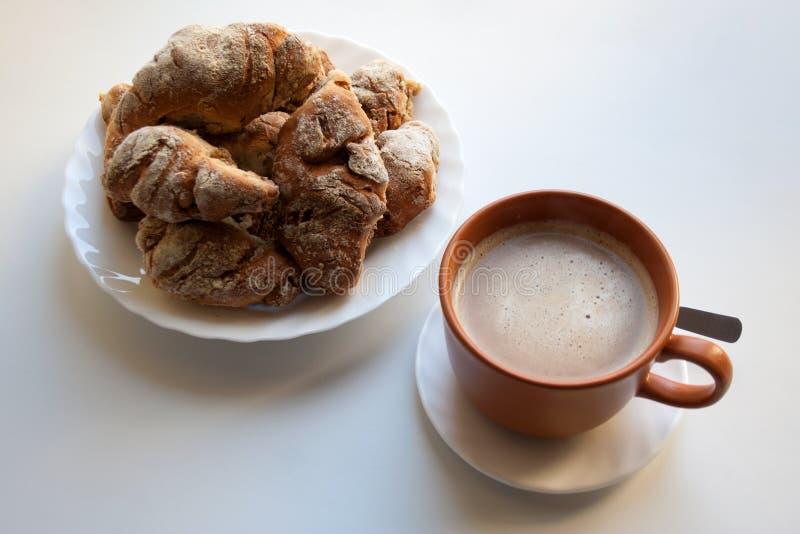 Montón de cruasanes y de la taza crujientes de café caliente imagen de archivo libre de regalías