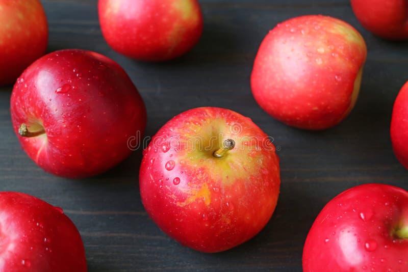 Montón de la manzana roja madura fresca con las gotitas de agua dispersadas en la tabla de madera marrón oscura fotografía de archivo
