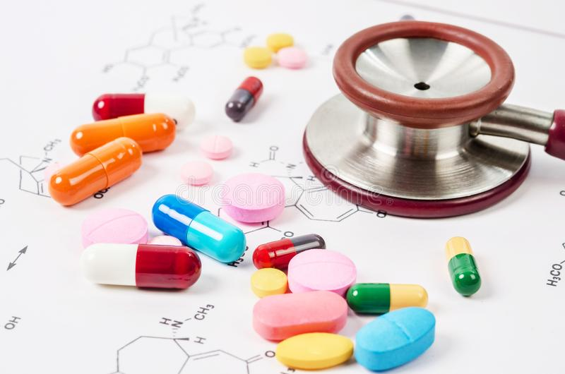 Montón de las píldoras y de las tabletas del color con el estetoscopio médico fotos de archivo